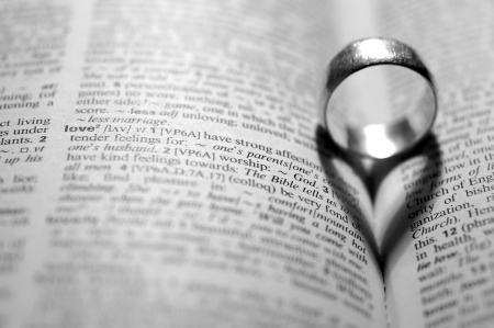 Word LOVE in a dictionary next to a heart-shaped shadow cast by a ring