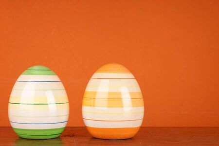 Two modern ceramic easter eggs in front of orange wall