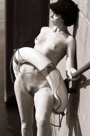 Foto de Lovely nude woman enjoying the sun at the harbour. - Imagen libre de derechos