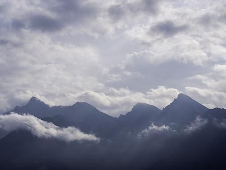 Photo pour Mountain range silhouette that break in an half in cloudy sky - image libre de droit