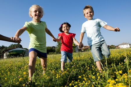Three children running holding hands