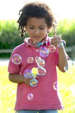 Little boy making soap bubbles