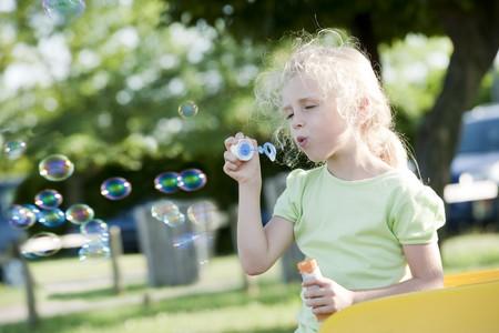 Cute little girl making soap bubbles in a park
