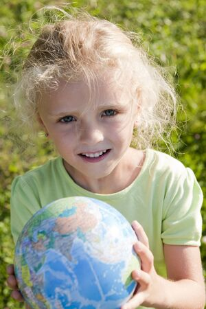 Little girl holding globe. Concept: Earth in future generations hands