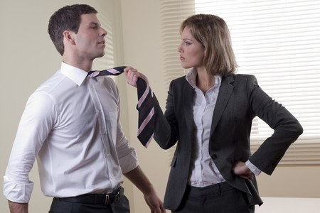 Business woman pullling his colleague from necktie