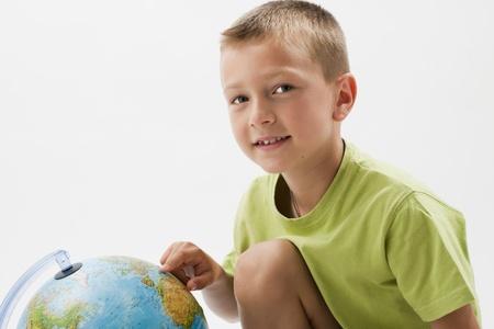 Photo pour Little boy with globe, looking at camera - image libre de droit