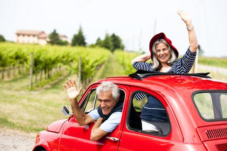 Photo pour Senior happy couple driving vintage car - image libre de droit