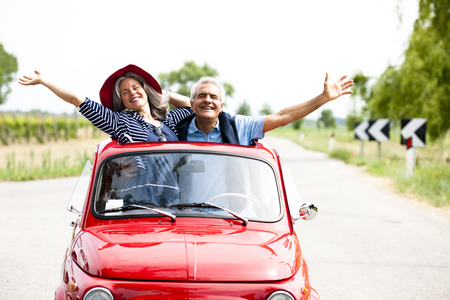 Photo for Happy senior couple driving vintage car - Royalty Free Image