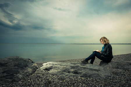 Woman writing her thoughts or poetry by the sea