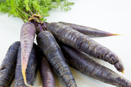 Foto für Bunch of heirloom purple carrots, over white and wooden background. - Lizenzfreies Bild