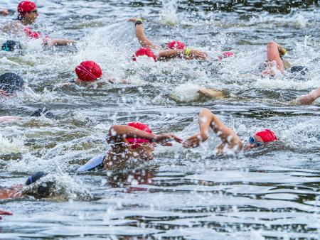 Photo pour Group of triathletes swimming in a lake - image libre de droit