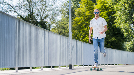 Young man with a longboard in an urban area