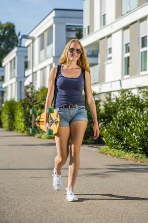 Young woman with a longboard in an urban area