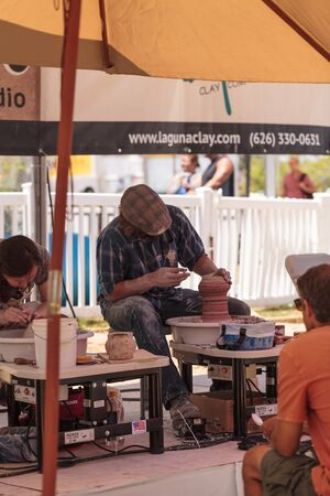 Costa Mesa, California, United States - July 16, 2016: Potters shape clay on a wheel at the display for Muddys Studio at the Orange County Fair.