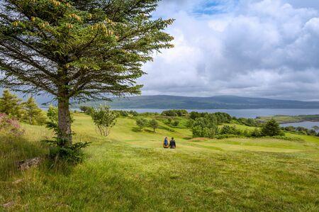 Photo pour Tourists couple walking at Islanf of Mull fields - image libre de droit