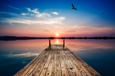 Perspective view of a wooden pier on the pond at sunset with perfectly specular reflection