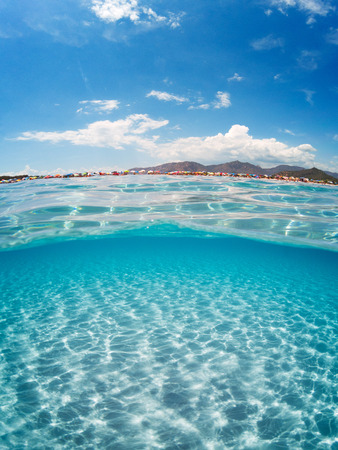Foto de Half underwater turquoise sea on summer day with a crowded beach - Imagen libre de derechos