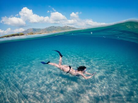 Photo pour Young beautiful girl diving underwater, on turquoise Sardinia sea. Half underwater photohraphy. - image libre de droit