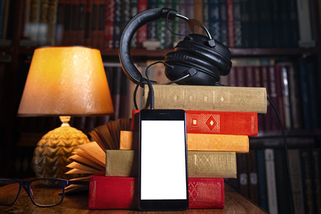 Photo for Mobile phone, headphones and a stack of books near the lamp. Concept of training and audiobooks. Library bookcase in the background. Close up and copy. Mock up. - Royalty Free Image