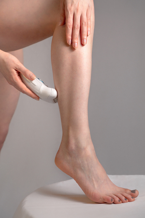 Photo pour A young woman removes excess hair with a depilator. Concept of skin care and Spa. Close up - image libre de droit