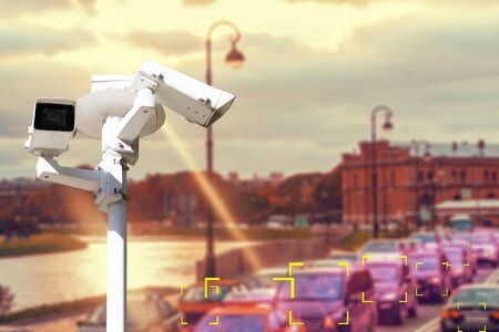 Photo for The concept of video surveillance and security technology. CCTV camera on the background of a road bridge with traffic in cloudy weather with a Sunny sunset. Color definition zone. - Royalty Free Image