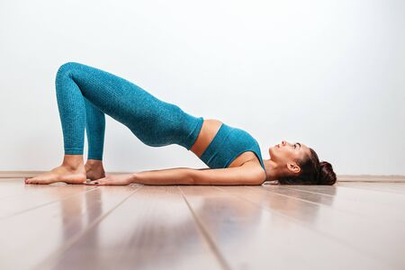 Foto für Yoga and sports concept. A young Caucasian woman is engaged in warm-up, performing the exercise bridge. White background in the background. Copy - Lizenzfreies Bild