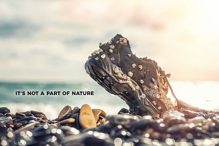 Photo pour Concept of environmental protection and pollution. An old Shoe, covered with shells, lies with its nose in the coastal rocks. The ocean is in the background. The inscription It's not a part of nature . Copy space. - image libre de droit