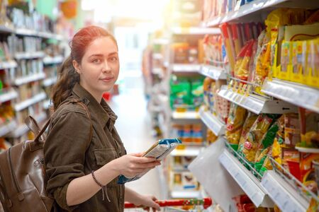 Photo pour Young pretty woman chooses healthy and quality products in the supermarket. Light. - image libre de droit
