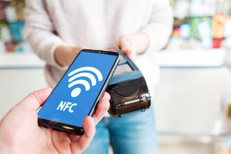 Photo pour The seller holds a payment terminal, and the man pays for the purchase using a smartphone, online. Top view. On the phone screen network. NFC concept, business and banking operations. - image libre de droit