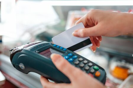 Photo pour The woman swipes a Bank card through the payment machine to complete the purchase payment. Hands close-up. NFC concept, business and banking operations. - image libre de droit