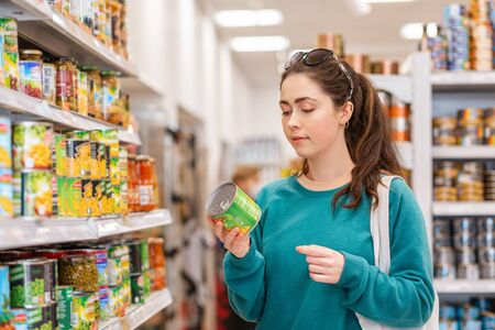 Photo pour A young pretty Caucasian woman reads ingredients on a tin of canned peas. The concept of buying products and shopping. - image libre de droit