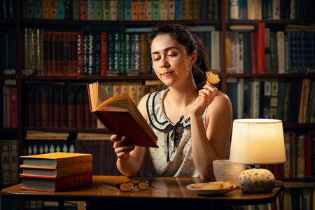 Photo pour A young pretty Caucasian woman holds a Cup of tea, eats cookies and reads a book. The concept of quarantine, distance learning and freelancing. - image libre de droit