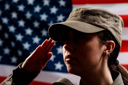 Foto per Memorial day. A portrait of female soldier in uniform salutes against the background of the American flag. Side view. The concept of the American national holidays and patriotism. - Immagine Royalty Free
