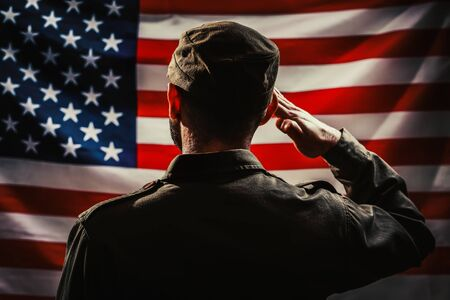 Foto per Memorial day. A uniformed soldier salutes against the background of the American flag. Rear view. Dark colors. The concept of the American national holidays and patriotism. - Immagine Royalty Free