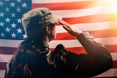 Foto per Veterans Day, Memorial Day, Independence Day. Silhouette of a female soldier saluting against the background of the American flag. Copy space. The concept of the American national holidays and patriotism - Immagine Royalty Free