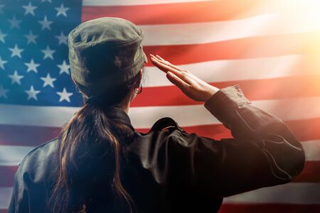 Foto per Veterans Day, Memorial Day, Independence Day. A female soldier salutes against the background of the American flag. Copy space. Rear view. The concept of the American national holidays and patriotism. - Immagine Royalty Free