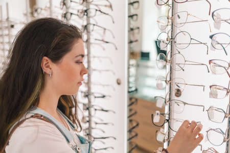 Photo pour Health and vision. A young and pretty woman chooses glasses in the salon of optics. - image libre de droit