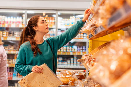 Photo pour Portrait of a young Caucasian woman reaches for the package to the top shelf. Store shelves in a blur, in the background. The concept of buying goods and shopping. - image libre de droit
