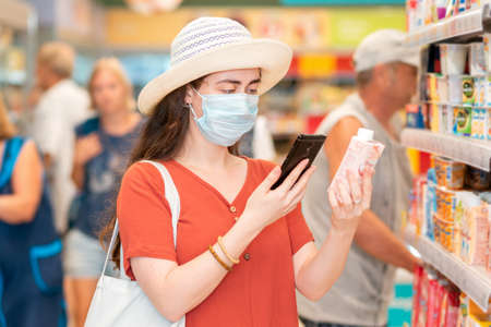 Photo pour Portrait of young woman in a medical mask scans the qr code on the product using her smartphone. In the background is a supermarket. The concept of modern technology and shopping during the pandemic. - image libre de droit