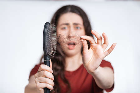 Photo pour Portrait in a blur, a screaming brunette woman holds a comb in front of her, clearing it from a pile of fallen hair. White background. Concept of hair loss, baldness and hair care. - image libre de droit