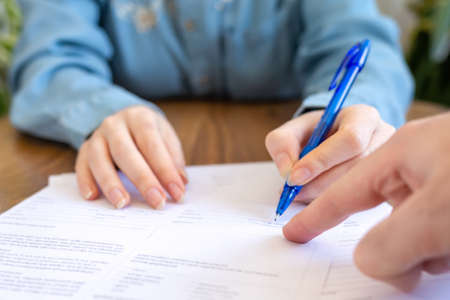 Photo pour World leasing day. The employee points his finger at the contract where you need to sign it. Hands close-up. Rental and purchase of real estate. - image libre de droit