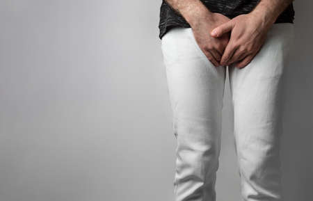 Photo pour The man in white jeans folded his hands at the level of his genitals. Disease for men. The concept of protection against sexually transmitted infections. Copy space. - image libre de droit