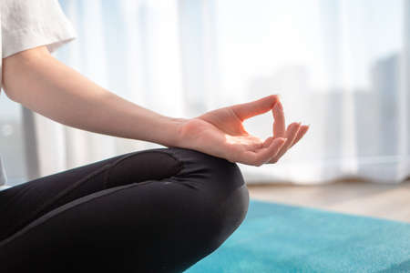 A woman is engaged in meditation. Close up of the hand. Indoor.