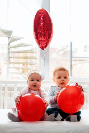 Photo for Valentine's day. Baby boy and baby girl sitting in a crib with red balls in their hands. Vertical orientation. - Royalty Free Image
