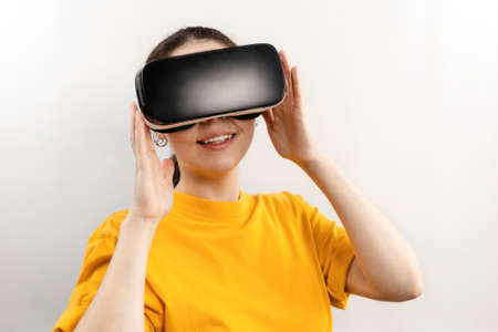 Foto de Virtual Reality concept. Portrait of a young smiling woman in virtual reality glasses. White background. - Imagen libre de derechos