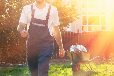 Photo pour close-up of a man in a blue uniform at sunset, in motion, the gardener finished the work .cart with bags and rake in the background. - image libre de droit