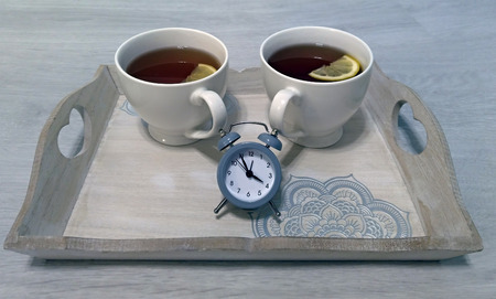 Conceptually - tea time - with two cups of tea and a clock - 4 o'clock in England