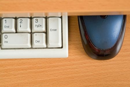 Office details. Computer keyboard and mouse on a wooden table.