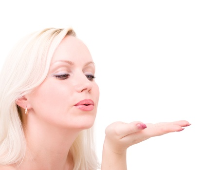 Young blonde woman blowing while sending an air kiss against a white background