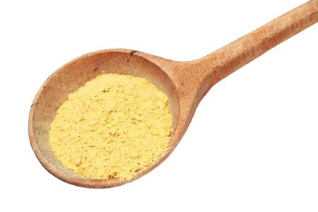 Nutritional yeast flakes in a wooden spoon isolated on white
